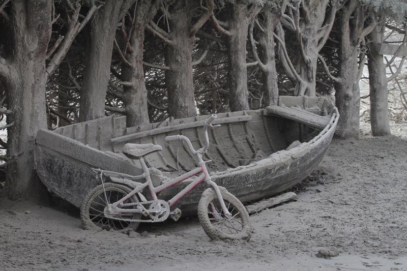 Un bote y una bicicleta cubiertos de cenizas del volcán Puyehue, en Bariloche, provincia de Río Negro, Argentina, en junio de 2011. Fotografía de Francisco Ramos Mejía (AFP).