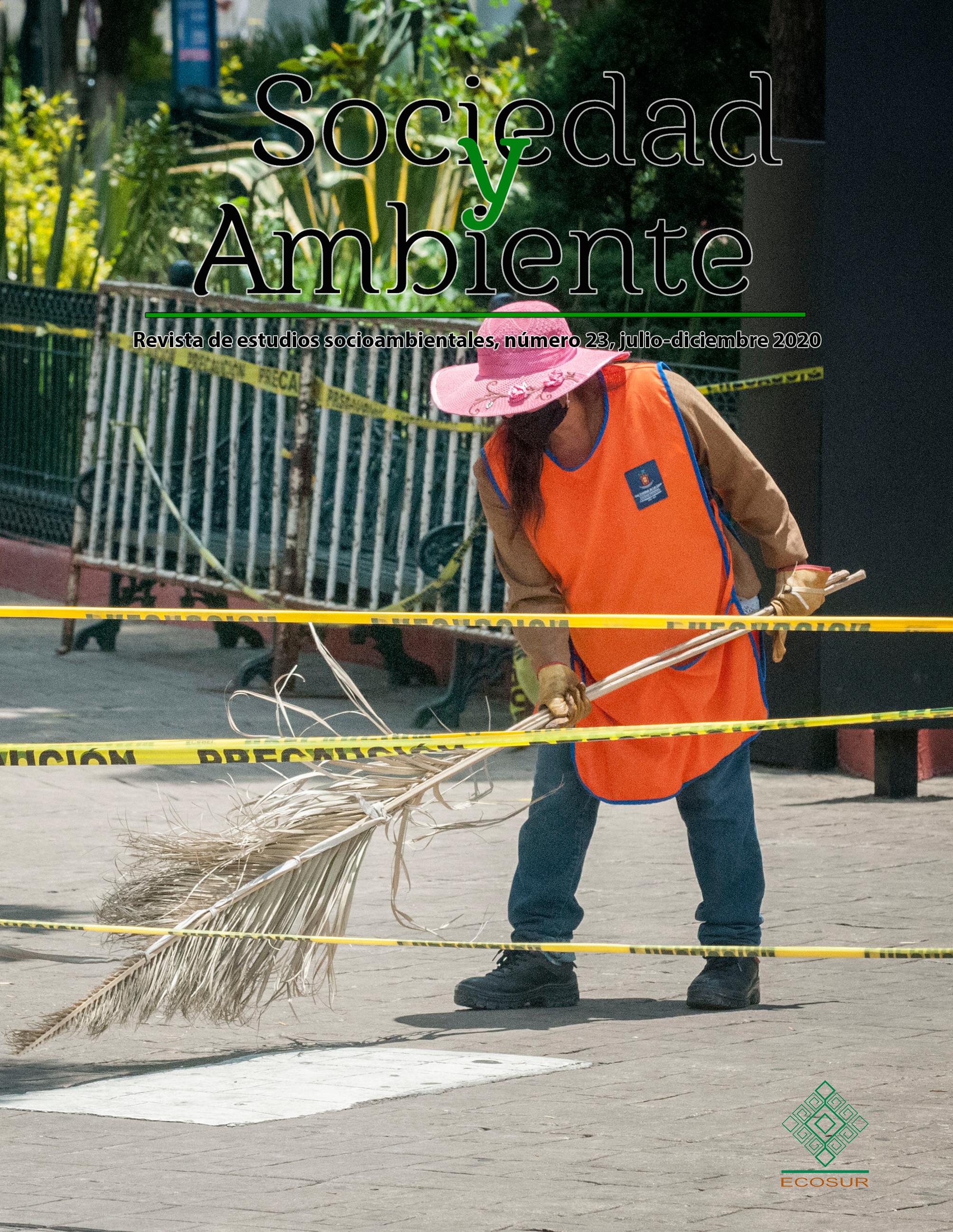 """En la plaza central de San Cristóbal de Las Casas cercada con letreros de """"peligro"""", una empleada pública barre con una escoba de palma y portando un cubrebocas."""
